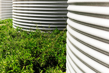 Large water collection tanks beside lush green bush.