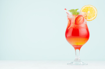 Fresh tropical red, yellow cocktail sunrise with slice orange, strawberry, ice, mint in misted wineglass on white wood table, blue  wall.