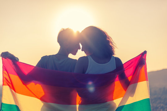 Beautiful lesbian couple with rainbow flag. Romantic relationship. Gender equality, family lifestyle.