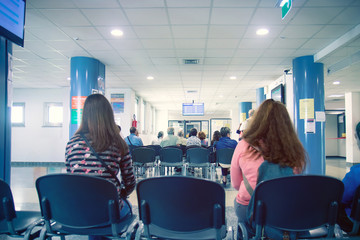 people in a waiting room of hospital, men and women wait their turn