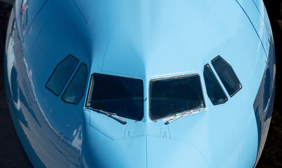 Closeup of the windows of a blue  airplane cockpit