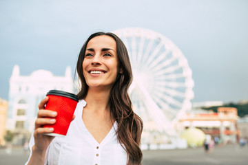 Happy cute young smiling woman is drinking coffee while walking in the city