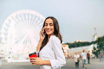 Cute young smiling woman talking on smartphone and drinking coffee while walking in the city