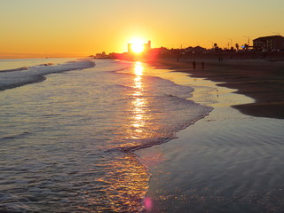A gorgeous sunset in Galveston Island in Texas while waves gently wash ashore