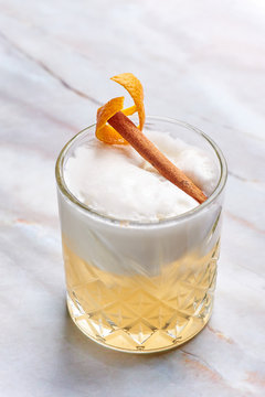 whisky sour alcohol cocktail with egg white, orange cedar and cinnamon