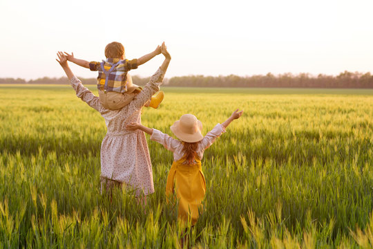 Happy family, mom, son and girl in straw hat in wheat field at sunset.  The concept of organic farming and healthy lifestyle, healthy food, happiness and joy