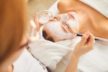 Young girl receiving white facial mask in spa beauty salon.