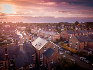 Sun setting with atmospheric effect over traditional British houses and tree lined streets. Dramatic, warm lighting creates a homely mood