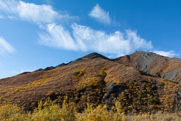Triangluar shaped ridge line is covered in  dark rock covered with browns and golds of an Alaskan fall