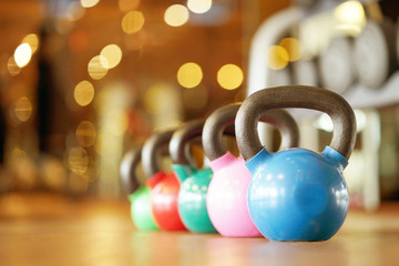 Colorful kettlebells in a row in a gym. Toning