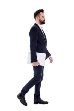 side view of young handsome bearded businessman with laptop walking isolated on white
