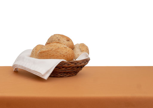Bread basket. Wholemeal brown bread rolls with white cloth, serviette aka napkin. Isolated against white behind.