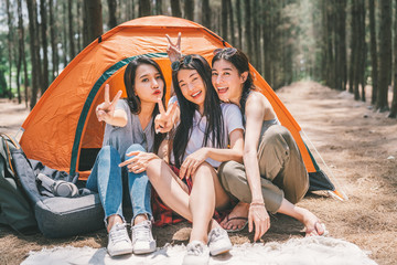 Group of happy Asian teenage girls doing victory pose together, camping by the tent. Outdoor activity, adventure travel, or holiday vacation concept