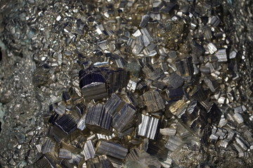 Raw Pyrite cluster rough crystals close up in low light background