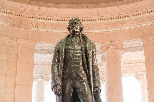 Bronze statue of Thomas Jefferson in Jefferson Memorial in Washington DC as setting sun illuminates interior of the monument