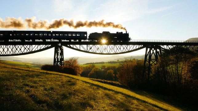 Historical Retro Steam Engine Train Driving on Railroad Track