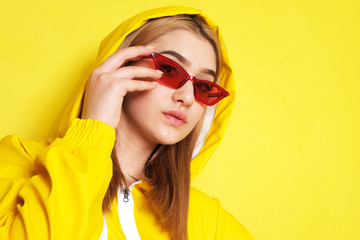 Pretty young girl with red glasses, and yellow hood on.