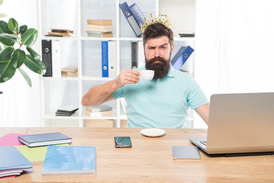 selfish secretary. selfish businessman in gold crown. selfish man drink coffee. Boss or secretary workplace. Bearded selfish man in business office. egoist. wishing to be big boss. reward and success