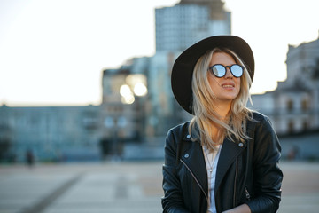 Outdoor fashion portrait of a cheerful blonde woman wearing hat and mirror sunglasses. Space for text Wall mural
