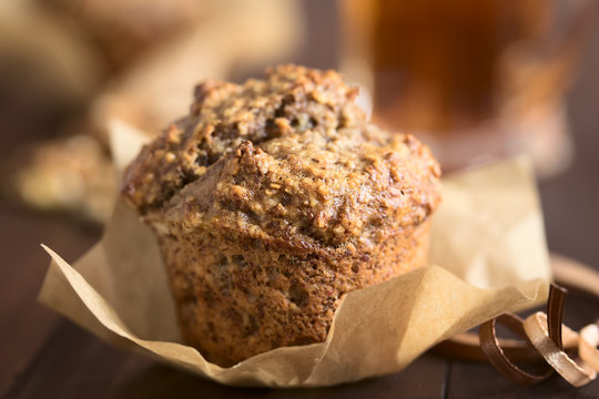 Fresh homemade oatmeal banana and walnut muffin, photographed with natural light (Very Shallow Depth of Field, Focus on the top front edge)
