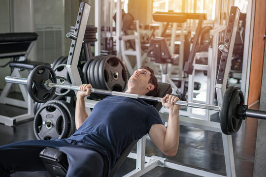 Handsome weightlifter lifting barbells bench press working out with curl bar in the gym