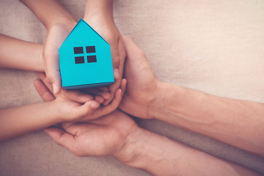 Adult and child hands holding blue paper house for family home and homeless shelter, social distancing, stay at home concept