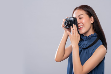 Portrait of asian woman using a vintage camera on white background, side view, Free from copy space. Photography in action.