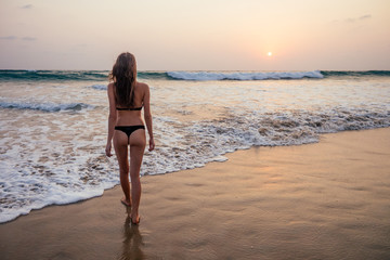 young woman in sexy swimming suit black thong in sea wawes having fun at sunset Goa beach India ocean