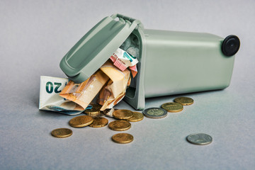 Europe financial crisis concept - closeup of Euro banknotes and coins in the garbage can