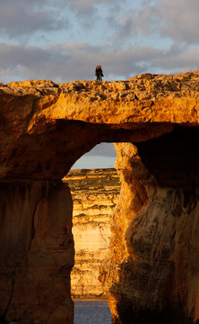 Tourists walk over the Azure Window, a 50 metre high rock arch, at Dwejra Point cliffs on the west coast of the Maltese island of Gozo