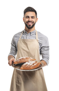 Baker with fresh bread on white background
