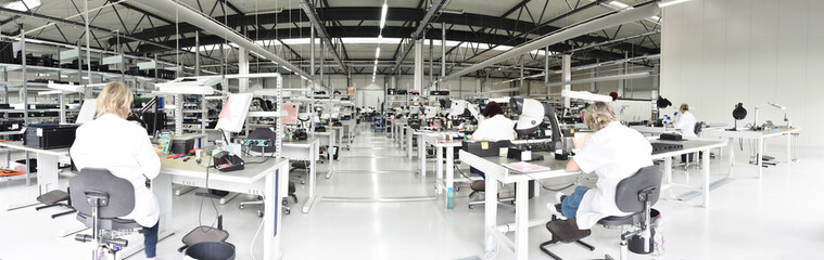 workers in a factory for the production of electronics - modern industrial enterprise
