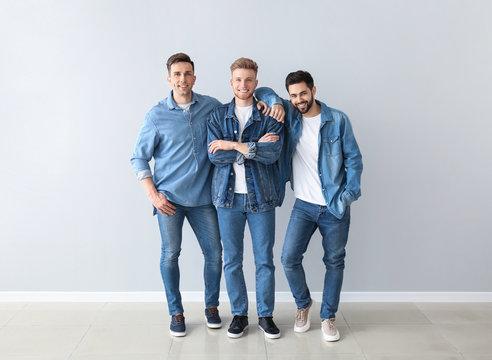Fashionable young men near light wall