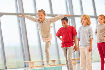 Mädchen trainiert Balance auf Schwebebalken