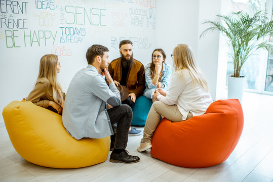 Group of diverse people sitting in a circle during the psychological therapy in the modern office. Feeling support from each other