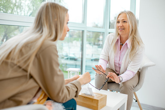 Senior female psychologist or mental coach giving advice to a young woman patient during the psychological meeting in the office
