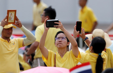 Woman takes pictures outside the balcony of Suddhaisavarya Prasad Hall at the Grand Palace where  of King Maha Vajiralongkorn will grant a public audience to receive the good wishes of the people in Bangkok