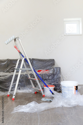 Room With Covered Sofa And Painting Equipment Ready For Wall
