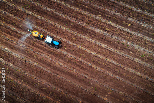Wall mural Aerial view of tractor spraying vineyard with fungicide.
