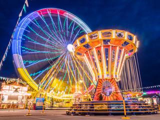 Riesenrad und Kettenkarussell am Abend auf dem Jahrmarkt