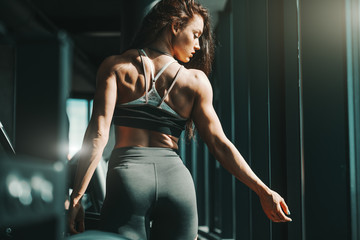 Portrait of beautiful Caucasian female bodybuilder posing in gym with back turned. Believe in yourself.