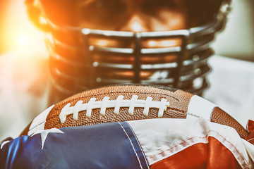 American football concept. The ball for the American football lies on the flag of America against the background of the portrait of the American football player.