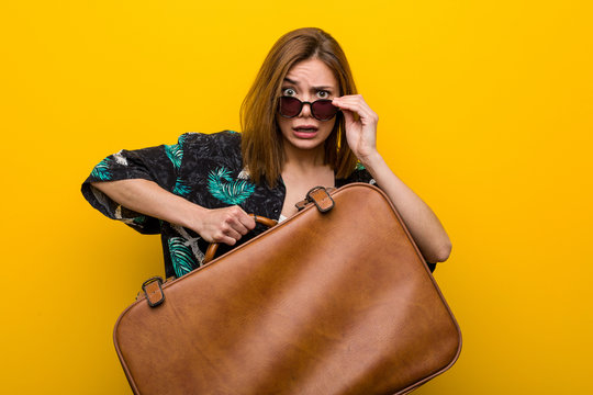 Young woman holding a leather bag  scared about her vacations, she has fobia to fly.