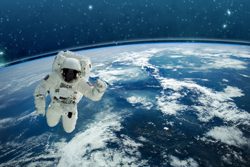 Picture of astronaut in space. In background planet Earth. Elements of this image furnished by NASA - Image