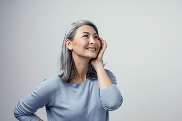 Side profile of charming asian woman smiling on white background Wall mural