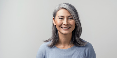 Beautiful asian with grey hair smiling standing near the wall Fototapete