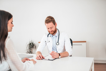 Doctor writing application form while consulting female patient in the office.