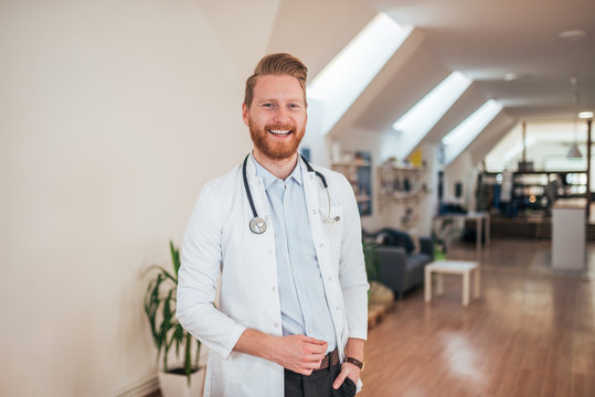 Portrait of young cheerful doctor in bright office.