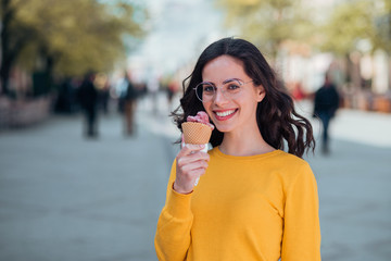 Portrait of a casual smiling young woman eating ice cream in the springtime in the town street.