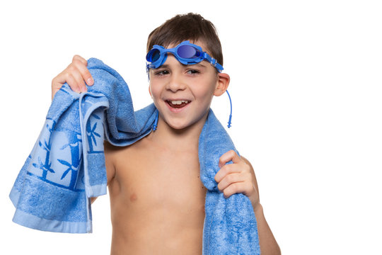cheerful boy, with blue swimming goggles on his head and with a blue towel on his shoulders, laughs, concept, on a white background